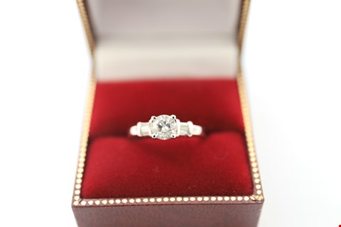 Lot 22 18CT WHITE GOLD RING SET WITH A DIAMOND AND BAGUETTES TO THE SHOULDERS. tOTAL DIAMOND WEIGHT +-0.91CT