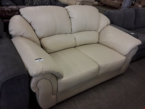 Lot 93 DESIGNER CREAM FAUX LEATHER TWO SEATER SOFA