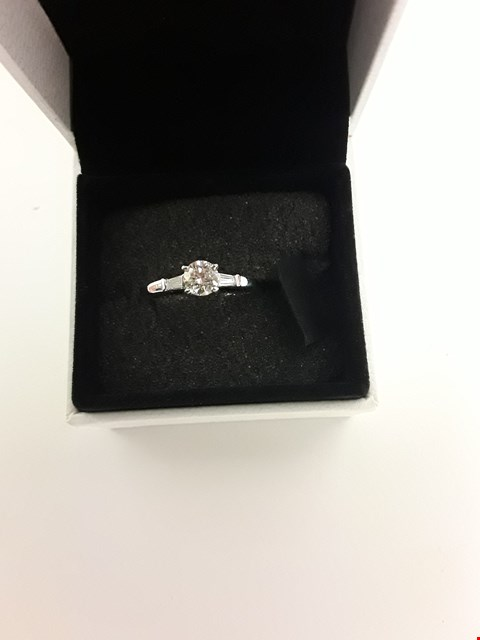 Lot 280 18CT WHITE GOLD RING SET WITH A DIAMOND TO CENTRE & BAGUETTES TO SHOULDERS. TOTAL WEIGHT +/- 0.65 CT
