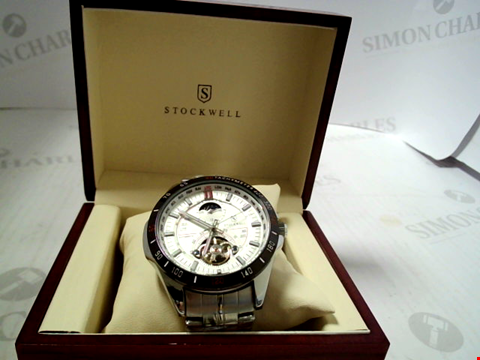 Lot 3296 DESIGNER STOCKWELL AUTOMATIC WATCH, MOONPHASE DIAL FOR AM/PM INDICATOR STAIINLESS STRAP. GLASS BACK RRP £650.00
