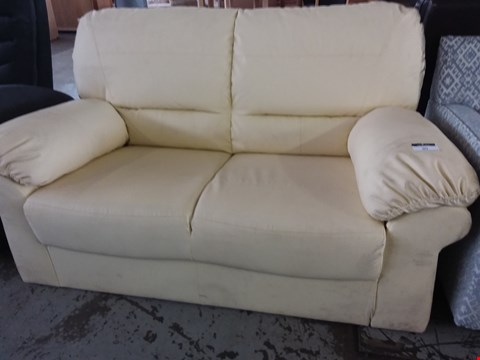 Lot 90 DESIGNER CREAM FAUX LEATHER 2 SEATER SOFA
